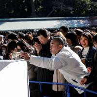 A man throws money into a giant offering box on the first day of the new year at Meiji Shrine in Tokyo on Jan. 1, 2017. Atago Shrine in Minato Ward is now accepting electronic money as donations. | REUTERS