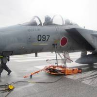 An Air Self-Defense Force F-15 fighter jet sits on the runway at Naha Airport after developing trouble in its front-landing gear Monday. | ASDF/ VIA KYODO