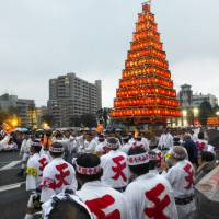People carry a giant float with multiple tiers of lanterns during the Tobata Gion festival in Kitakyushu on Dec. 4. While the festival is among the 33 recently added to the UNESCO Intangible Cultural Heritage list, a lack of people to inherit traditions has led to the abolishment and suspension of many lesser-known local festivals across Japan. The Kitakyushu event, usually held in summer, was held last month to celebrate its UNESCO list inclusion. | KYODO