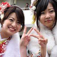 This picture taken Monday shows 20-year-olds flashing the 'peace' sign, a common picture pose in Japan, while taking a photograph before their 'Coming-of-Age' ceremony at the Tokyo Disneyland in Urayasu, Chiba Prefecture. | AFP-JIJI