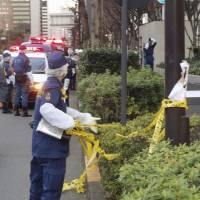 Police investigate outside the industry ministry in Tokyo where a 78-year-old man allegedly started a shrubbery fire on Monday. KYODO