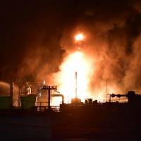 Flames and smoke are seen Sunday night at a TonenGeneral Sekiyu K.K. refinery in the city of Arida, Wakayama Prefecture, after a fire broke out during the afternoon.   KYODO