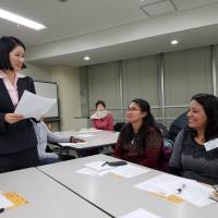 Foreign volunteers hone their translation skills in a class taught by a professional interpreter in Itabashi Ward, Tokyo, on Saturday — the latest in a series of workshops organized by the Asian People's Friendship Society. | TOMOHIRO OSAKI