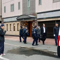 Police examine a street in front of a hotel in the city of Fukuoka on Wednesday after a man jumped to his death from a room on the seventh floor. | KYODO
