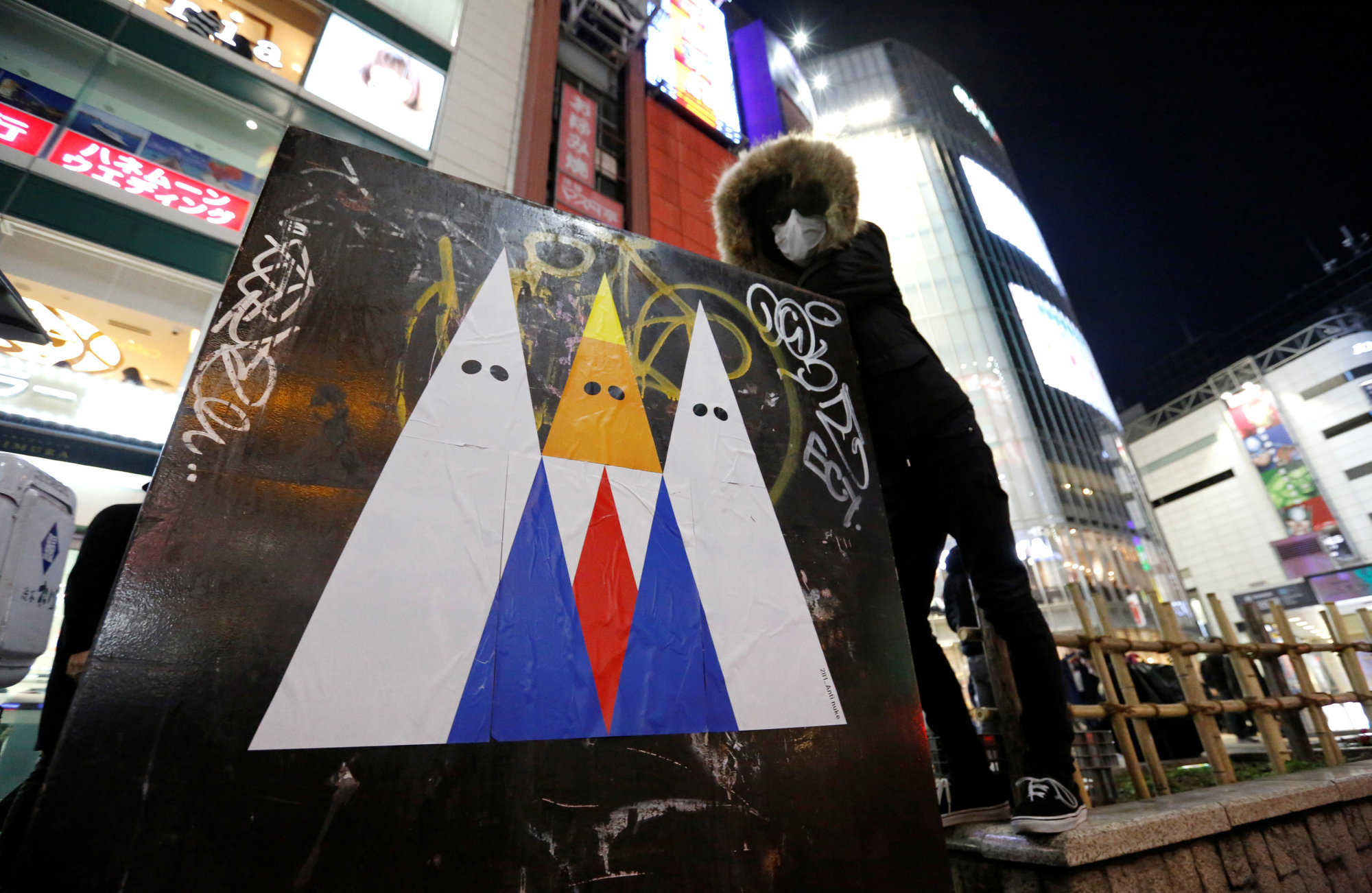 A graffiti artist known as 281_Anti Nuke poses for a photo next to an example of his recent artwork depicting U.S. President Donald Trump, in Tokyo's Shibuya district on Friday. | REUTERS