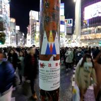 Sticker art depicting U.S. President Donald Trump, made by a Japanese graffiti artist known as 281_Anti Nuke, is seen at the busy crossing in Tokyo's Shibuya area.