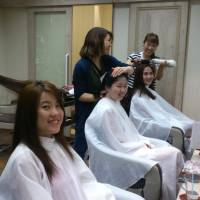 Chinese tourists get their hair cut at the salon grace by afloat, operated by Forcise, in Osaka in July 2015. | COURTESY OF FORCISE