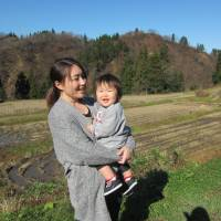 Kanako Sato stands with her daughter by terraced paddy fields in the city of Tokamachi, Niigata Prefecture, on Nov. 26. | KYODO