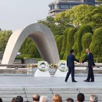 U.S. President Barack Obama shakes hands with Prime Minister Shinzo Abe at the Hiroshima Peace Memorial when he visited the atomic-bombed city last May as the first sitting U.S. president to do so. | KYODO