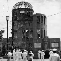 This photograph, taken on Sept. 8, 1955, just over 10 years after the bombing of Hiroshima, shows U.S. Navy sailors looking at what is now called the A-Bomb Dome. | HIROSHIMA PEACE MEMORIAL MUSEUM / VIA KYODO