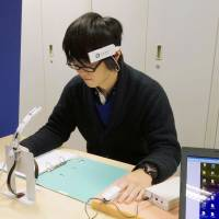 A student at Kagawa University participates in an experiment in which his brain and heart data are scanned while he smells Japanese incense. | KYODO