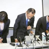 Shinya Yamanaka (center), director of the Center for iPS Cell Research and Application at Kyoto University, bows in apology at a news conference in Kyoto on Monday.