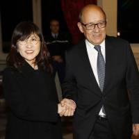 Defense Minister Tomomi Inada is welcomed by French Defense Minister Jean-Yves Le Drian ahead of talks in Paris on Friday. | AFP-JIJI