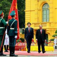 Prime Minister Shinzo Abe and his Vietnamese counterpart, Nguyen Xuan Phuc, review an honor guard at the Presidential Palace in Hanoi on Monday. | REUTERS