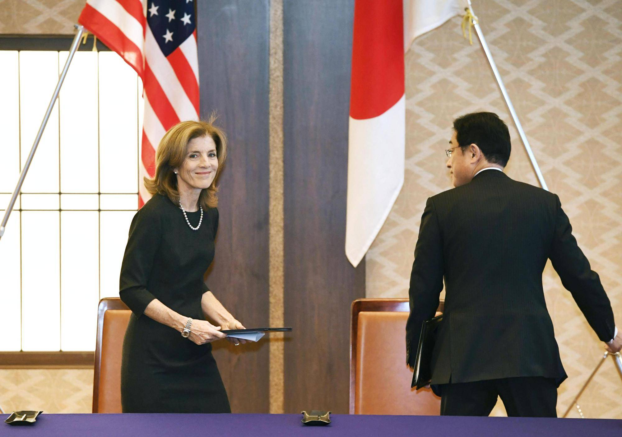 U.S. Ambassador Caroline Kennedy leaves a news conference in Tokyo with Foreign Minister Fumio Kishida on Monday after signing a deal to clarify the definition of civilian base workers protected under the Status of Forces Agreement. | KYODO