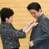 Tokyo Gov. Yuriko Koike attaches a 2020 Tokyo Olympics and Paralympics badge to the jacket of Prime Minister Shinzo Abe before their meeting at his office in Tokyo on Tuesday. | KYODO