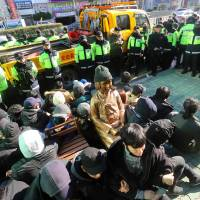 This picture taken on Dec. 28, 2016, shows South Korean activists staging a sit-in protest around a statue in Busan of a teenage girl symbolizing former 'comfort women' who served as sex slaves for Japanese soldiers during World War II. | AFP-JIJI