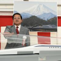 JR Tokai President Koei Tsuge poses before a replica of a maglev train on Dec. 17, 2014, at Nagoya Station. | KYODO