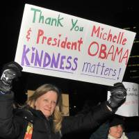 A participant in the Friday march in Tokyo holds up a sign to express gratitude to outgoing U.S. President Barack Obama. | YOSHIAKI MIURA