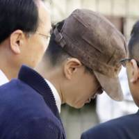 Accompanied by investigators, Pak Jung-hyun, an editor at major publisher Kodansha Ltd., leaves his home in Tokyo to go to a police station Tuesday over the suspicious death of his wife. | KYODO