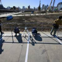 Photographers shoot the site of the planned new national stadium in Tokyo after a groundbreaking ceremony was held in December. | AP