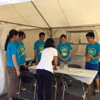 Members of student volunteer group Team Medics provide medical help at the Global Festa Japan event in October 2015. | COURTESY OF TEAM MEDICS