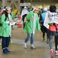 Volunteers offer linguistic support for foreigners who participated in the Tokyo Marathon in February 2016. Japan is struggling to overcome language and cultural barriers as Tokyo gears up for the 2020 Olympics and Paralympics. | KYODO