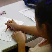 A staffer at an education support facility for children in poverty run by the Fukuoka Prefectural Government teaches math to a child last May. | KYODO