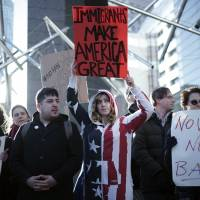 Americans and other expats gather to protest against President Donald Trump's recent travel ban, outside the U.S. Embassy in Tokyo on Tuesday. | AP