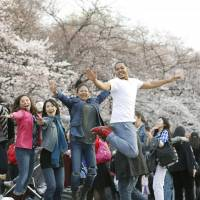 People jump for joy at Tokyo's Ueno Park, one of the most famous cherry-blossom viewing sites. | KYODO