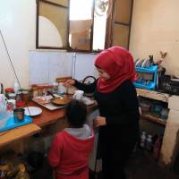 Children who fled from Syria prepare food in their family's kitchen at the Shatila Palestinian refugee camp on Jan. 7. Last May, Prime Minister Shinzo Abe said Japan will accept up to 150 Syrian refugees as students over the next five years. | AFP-JIJI