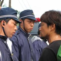 A still photograph from the documentary 'Takae — Mori ga Naiteiru' depicts clashes between riot police and local residents opposing construction of U.S. helipads near a U.S. military training site in Takae, Okinawa, in July. | ©MORINOEIGASHA