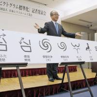 Madoka Kitamura, head of the Japan Sanitary Equipment Industry Association, shows unified pictograms for the member companies' toilets in Chiyoda Ward, Tokyo, on Tuesday. | KYODO