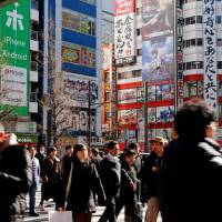 People cross a street in the Akihabara shopping district in Tokyo on Tuesday. The 22 percent increase in the number of international visitors to Japan from the year before is smaller than the 48 percent surge logged in 2015. | REUTERS