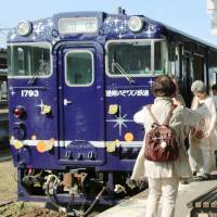 Tourists board the Nagamare Kaikyo sightseeing train at JR Hakodate Station in Hokkaido last May. | KYODO