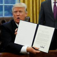 U.S. President Donald Trump holds up the executive order of withdrawal from the Trans-Pacific Partnership after signing it in the Oval Office on Monday. | REUTERS