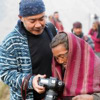 Checking the shot: Bon Ishikawa shows a Nepalese woman one of his pictures. | REI MIYAMOTO