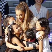 Ariana Grande interacts with fans during a tour to Japan. | AP