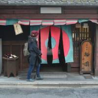 Crossing the threshold: A woman walks through hanging curtains to enter Daigokuden, a sweets shop in Kyoto. | J.J. O'DONOGHUE