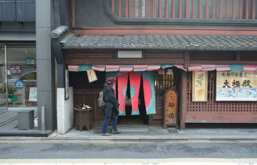 Crossing the threshold: A woman walks through hanging curtains to enter Daigokuden, a sweets shop in Kyoto.