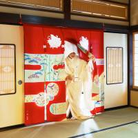 A woman dressed in a bridal outfit enters a room a through a noren at the Bridal Curtain Museum in Nanao, Ishikawa Prefecture. | COURTESY OF THE BRIDAL CURTAIN MUSEUM
