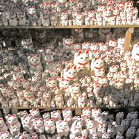 Maneki-neko cat figurines wave at visitors to Gotokuji Temple. | KIT NAGAMURA
