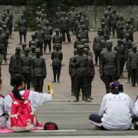 Students sit at the Chinese Heroes Statues Plaza, which displays war heroes from the War of Resistance against Japan, in Jianchuan Museum Cluster in Anren, Sichuan Province. | REUTERS