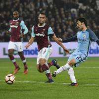 Manchester City's David Silva scores against West Ham in an F.A. Cup match on Friday in London. | REUTERS
