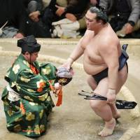 Kisenosato (right) is seen after beating Ichinojo on Saturday, the 14th day of the New Year Grand Sumo Tournament at Ryogoku Kokugikan. Kisenosato (13-1) secured his first career title with the win over Ichinojo. | KYODO