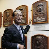 New inductee Senichi Hoshino looks at the plaques on the wall of the Baseball Hall of Fame earlier this week. | KYODO
