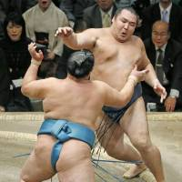Kakuryu (top) backpedals during his defeat to Tamawashi at the New Year Grand Sumo Tournament on Tuesday. | KYODO