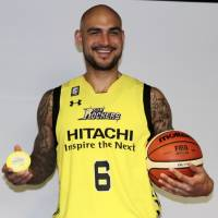 New Sunrockers center Robert Sacre holds a basketball and a cup of shaved ice as he poses for photos during a news conference on Thursday in Shibuya. | KAZ NAGATSUKA