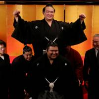 New yokozuna Kisenosato (top) raises his arms in celebration as his sumo stablemates lift him up after a ceremony in Tokyo on Wednesday. | REUTERS