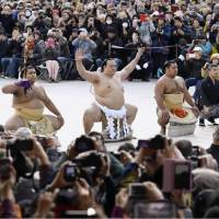 New yokozuna Kisenosato (center) performs his first ring-entry ceremony on Friday in front of a crowd of around 18,000 at Meiji Shrine. | KYODO